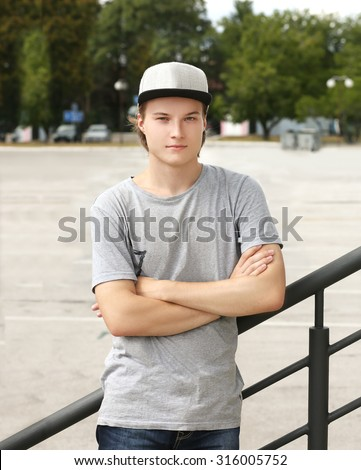 Portrait of attractive teenage boy standing with crossed arms against grey background - stock photo