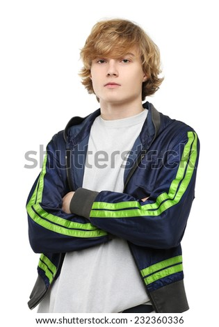 Portrait of attractive teenage boy standing with crossed arms against white background - stock photo