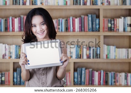 Portrait of attractive teenage girl standing in the library while holding a tablet with empty screen