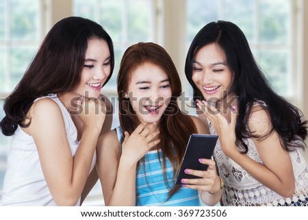 Portrait of attractive teenage girls looks amazed when reading message on mobile phone - stock photo