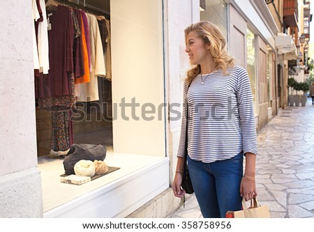 Portrait of attractive teenager girl walking in a city shopping street, looking at a fashion store window, smiling on a sunny day, outdoors living. Adolescent consumer and lifestyle, exterior. - stock photo