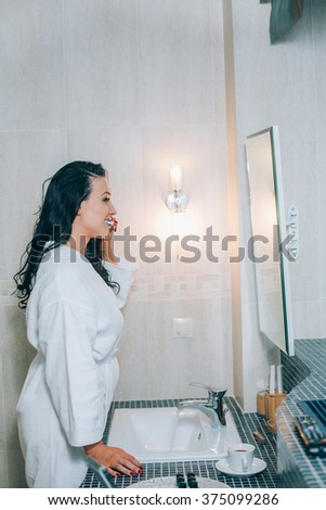 Portrait of attractive woman brushing teeth in bathroom  a white coat. healthy teeth. - stock photo