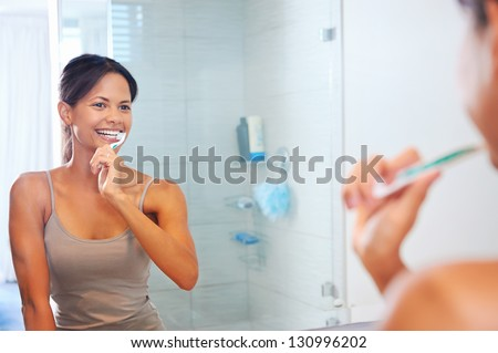 Portrait of attractive woman brushing teeth in bathroom and looking in the mirror at reflection. healthy teeth.