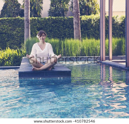 Portrait of attractive woman dressed in white sitting in meditating position by the pool