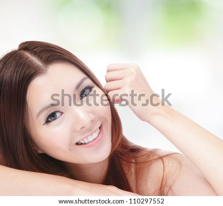 portrait of attractive woman happy smiling and hand touch face with nature green background, model is a asian girl - stock photo
