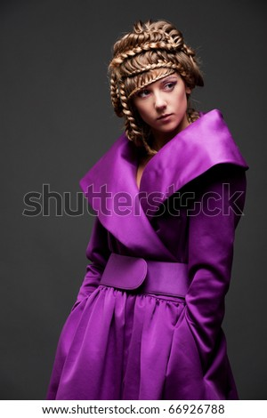 portrait of attractive woman in violet dress over dark background - stock photo