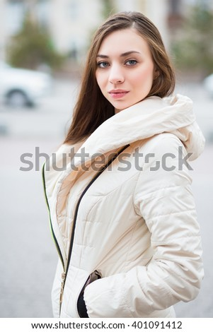 Portrait of attractive woman in white jacket posing outdoors - stock photo