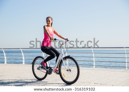 Portrait of attractive woman riding on bicycle outdoors near the sea - stock photo