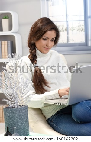 Portrait of attractive woman sitting at home using laptop computer, winter ambience. - stock photo