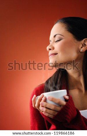 portrait of attractive woman smelling the aroma of fresh hot coffee with steam isolated on orange background - stock photo