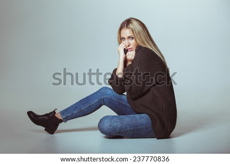 Portrait of attractive woman wearing sweater sitting on floor. Teenage girl looking at camera. - stock photo