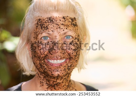 Portrait of attractive woman with a coffee pilling mask applied on the face for skincare and massage