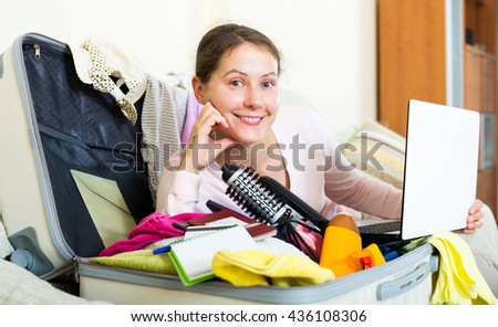 Portrait of attractive woman with packed baggage and notes - stock photo