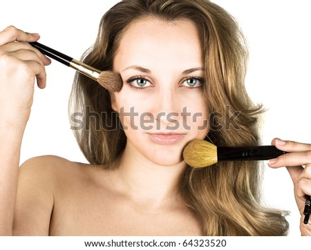 Portrait of attractive young adult woman applying blusher - stock photo