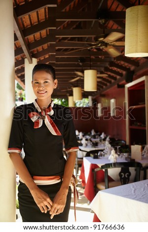 Portrait of attractive young asian woman working as waitress in exclusive restaurant. Waist up, front view - stock photo