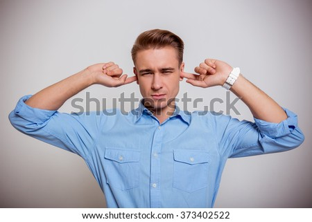 Portrait of attractive young blond businessman in blue shirt holding fingers in ears, standing against gray background
