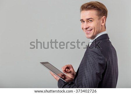 Portrait of attractive young blond businessman in classical suit smiling, looking in camera and using tablet, standing against gray background