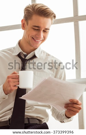 Portrait of attractive young blond businessman in white classical shirt and dark tie smiling, holding a cup and sheets of paper while standing near the window - stock photo