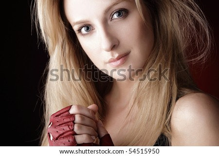 Portrait of attractive young blond smiling woman in sports gloves.