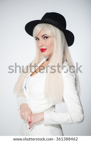 Portrait of attractive young blond woman standing and smiling. She is wearing black hat and white wig. The girl is looking at camera playfully. Isolated - stock photo