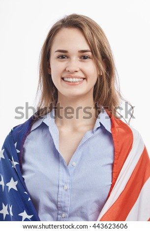 Portrait of attractive young brunette girl covered by National Flag celebrating Independence Day on 4th of July in United States of America.Cute model with toothy smile on isolated background - stock photo