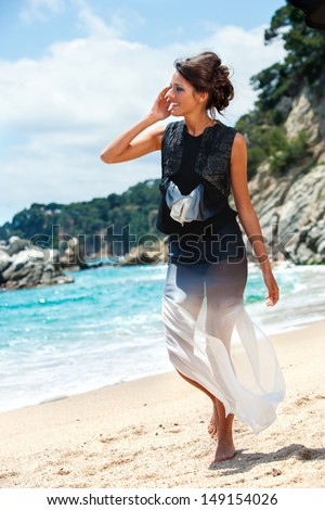 Portrait of attractive young brunette in elegant dress walking on beach. - stock photo