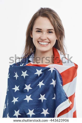 Portrait of attractive young brunette woman covered by National Flag celebrating Independence Day on 4th of July in United States of America.Cute model with toothy smile on isolated background - stock photo