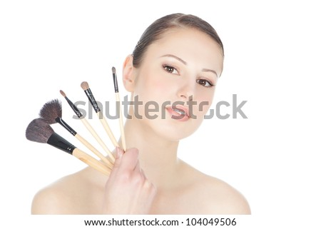 Portrait of attractive young brunette woman holding  make-up brushs over white