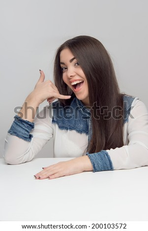 Portrait of attractive young brunette woman looking at you. Isolated on the grey background - stock photo