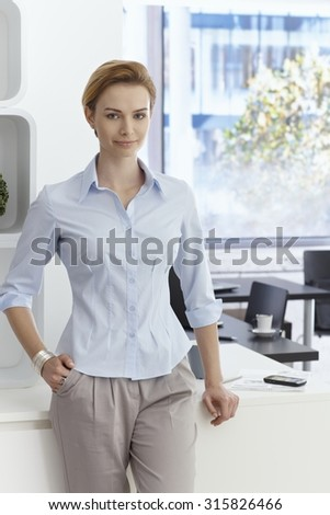 Portrait of attractive young businesswoman standing in office, smiling, looking at camera. - stock photo