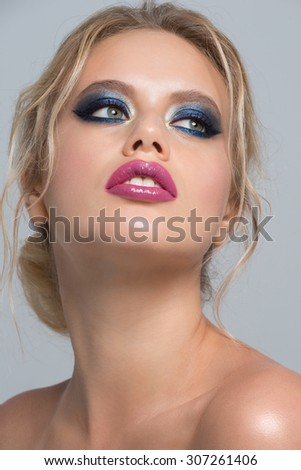 Portrait of attractive young caucasian woman with stylish blue makeup - stock photo