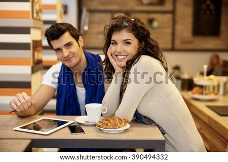 Portrait of attractive young couple in cafeteria, smiling happy, looking at camera. - stock photo