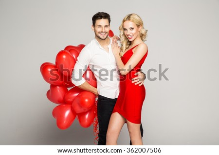 Portrait of attractive young couple posing on grey background and holding balloons heart. Valentine's day. - stock photo