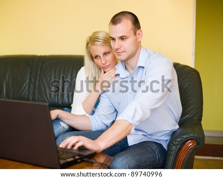 Portrait of attractive young couple shopping online using laptop at home. - stock photo