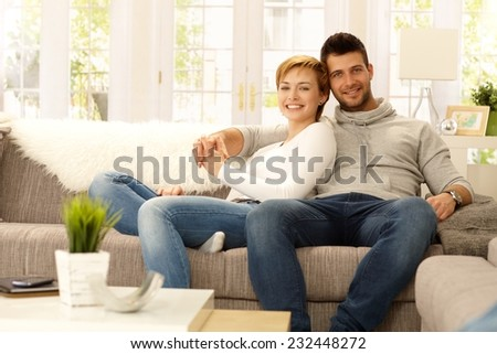Portrait of attractive young couple sitting on sofa at home, hugging, looking at camera, smiling.