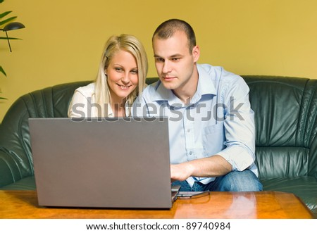 Portrait of attractive young couple using laptop at home. - stock photo
