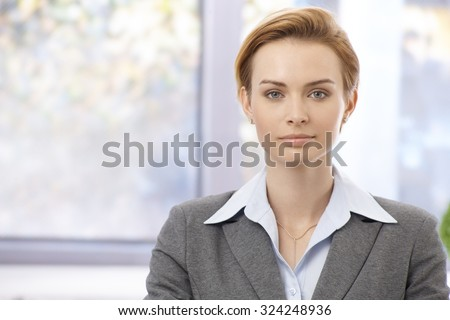 Portrait of attractive young elegant businesswoman looking at camera, serious. - stock photo