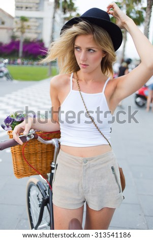 Portrait of attractive young female dressed in trendy summer clothes standing with her classic bicycle in urban setting, wonderful Sweden woman enjoying a rest after riding on retro bike in the city - stock photo