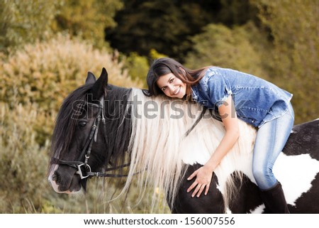 portrait of attractive young female rider embracing her horse and looking at camera - stock photo