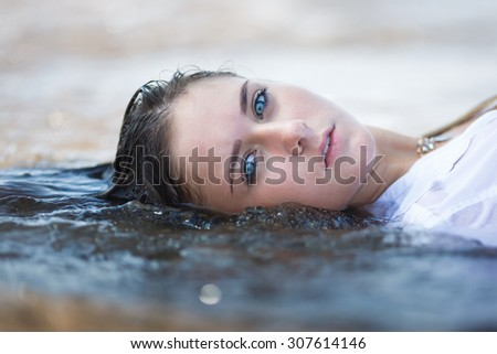 Portrait of attractive young girl in the water - stock photo