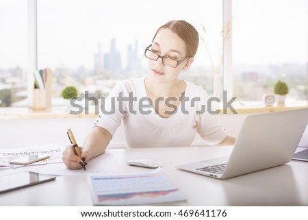 Portrait of attractive young lady doing paperwork at office desk with laptop, tablet, business report and other items