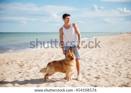 Portrait of attractive young man standing with his dog on the beach - stock photo