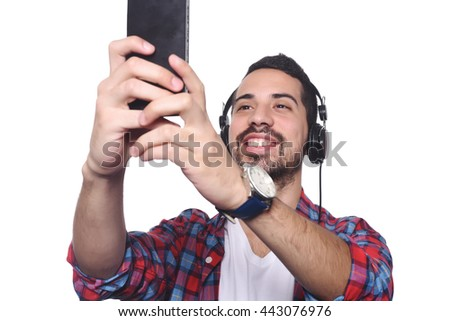 Portrait of attractive young man taking a selfie with his smartphone and black headphones. Isolated white background. - stock photo