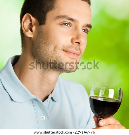 Portrait of attractive young man with glass of redwine, outdoor - stock photo
