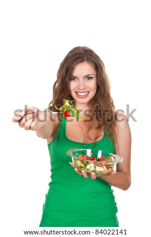 Portrait of attractive young smile woman eating vegetable salad, holding bowl and fork in hand, long brown hair, green shirt, isolated over white background - stock photo