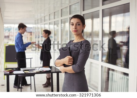 Portrait of attractive young success business woman with tablet in office with team colleague on background. Business cooperation, negotiations, problems solution - stock photo