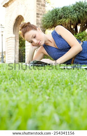 Portrait of attractive young tourist woman relaxing in a monument's park grass reading a travel guide book visiting a destination city on a summer holiday. Travel tourism and vacation lifestyle. - stock photo