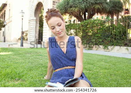 Portrait of attractive young tourist woman relaxing in a monument's park grass reading a travel guide book visiting a destination city on a summer holiday. Travel tourism and lifestyle. - stock photo