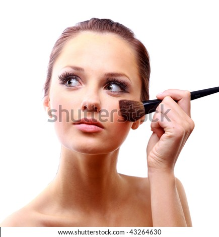 Portrait of attractive young woman applying blusher - stock photo