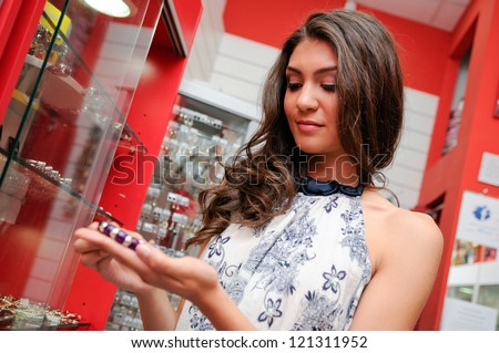 Portrait of attractive young woman buying a bracelet at a jewelry